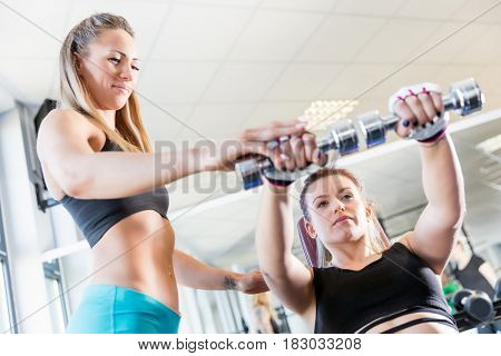 Personal trainer assistance during fatburning exercise at the gym. Healthy lifestyle and motivation concept.