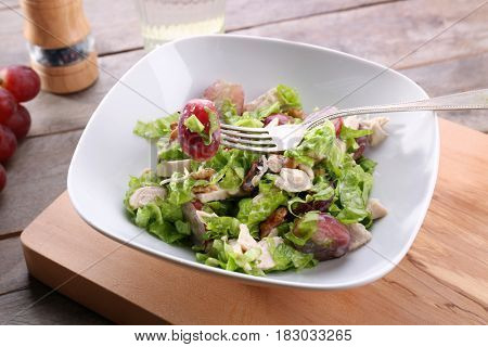Plate with chicken salad and grapes on table
