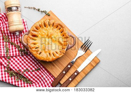 Delicious chicken pot pie in saucepan on wooden board