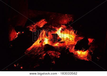 glowing red coals of campfire in the outdoors