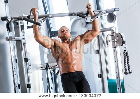 Muscular strong man working out at a gym.chinup training. Bodybuilding.