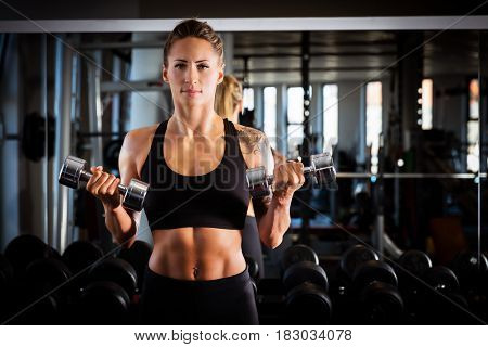 Attractive woman exercising at the gym. Body training, dumbbell workout. Healthy lifestyle.