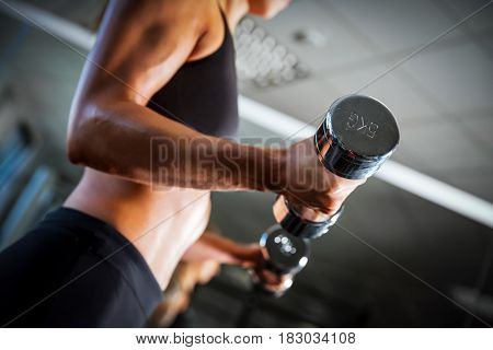 Fit woman exercising with dumbbells at the gym. Body training, weightlifting workout. Healthy lifestyle.