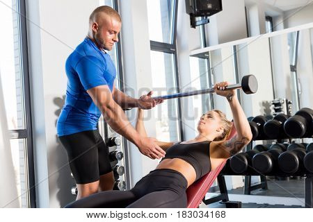 Personal trainer working with a client at the gym. Workout assistance and motivation. Sport concept.