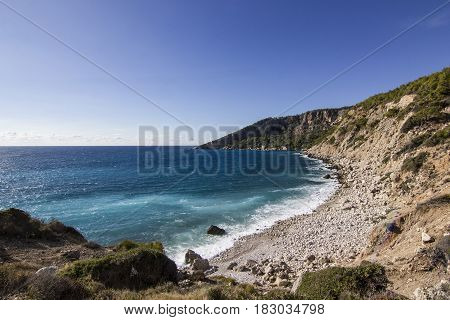 sun shining above mountains with blue sea in bay of mediterranian sea