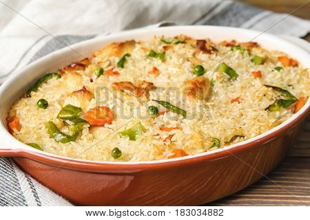 Tasty rice and chicken with vegetables in baking dish