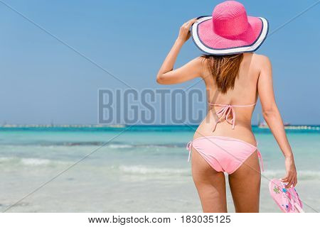 Beach vacation. Hot beautiful woman in sunhat and bikini standing with her arms raised to her head enjoying looking view of beach ocean on hot summer day. Photo from Hapuna beach Big Island Hawaii.