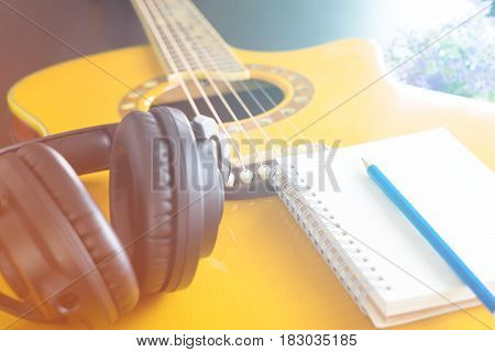 Guitar and Headphone with notebook for songwriting