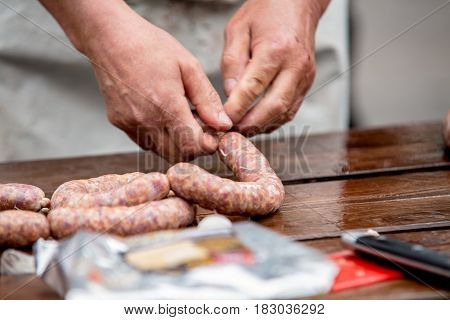 Butcher making tasty sausages in meat factory