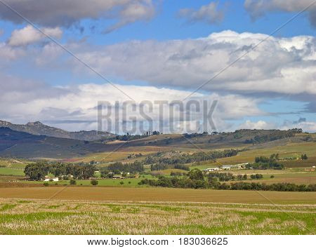 AN OPEN FIELD IN FORE THE GROUND WITH MOUNTAINS, TREES AND CLOUDS IN THE BACK GROUND