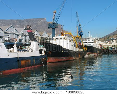 FROM CAPE TOWN, SOUTH AFRICA, SHIPS AND BUILDINGS IN THE FORE GROUND AND PART OF TABLE MOUNTAIN IN THE BACK GROUND 20drt