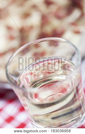 closeup of  a glass of white wine and flammkuchen