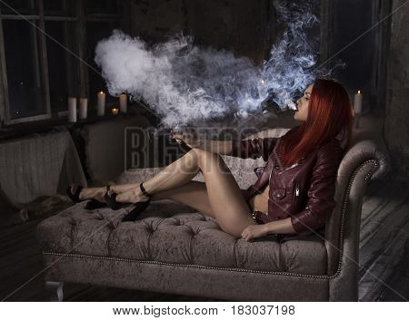 Sexy redhead woman vaping electronic hookah. Vape concept