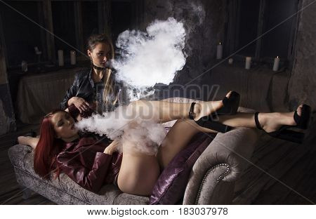 Sexy vaping vaponizer and clouding, women with sexy bodies lying on the sofa and smoke electronic hookah