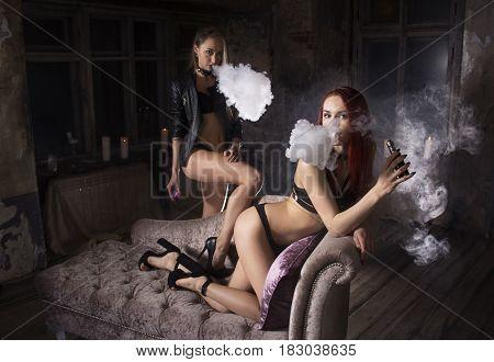 Vaping. Young sexy women smoking electronic hookah.Studio shooting