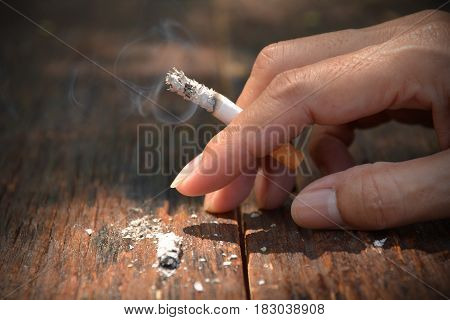 Tobacco cigarettes in hand on wooden background with light shines on the tobacco cigarettes.