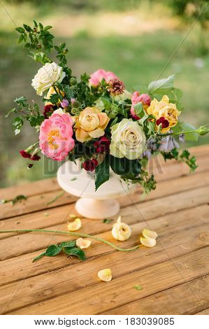 bouquet, holidays flower, gifts and floral arrangement concept - close-up on bouquet of cute yellow and white roses, pink charming peon, carnations, shoots of wild rose, white vase on wooden table