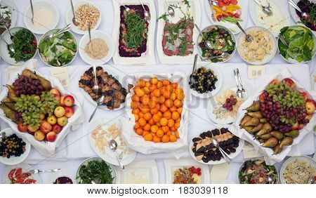 Top View Of Plates With Delicious Homemade Food , Garden Berries, Fruits, Cups And Cutlery On The Bi