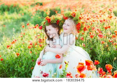 little girl model, wedding, poppies, summer fashion concept - two girls dressed in white and blue dress smiling in a field of red poppies, blonde hugged another, on heads of them wreaths of poppy