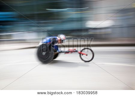 blurred image of wheelchair racer participating at marathon