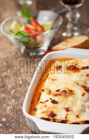 italian lasagna on a square plate on wood
