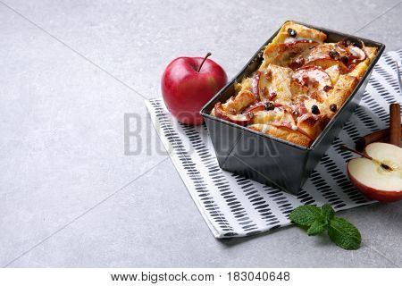 Freshly baked bread pudding in casserole dish on grey table