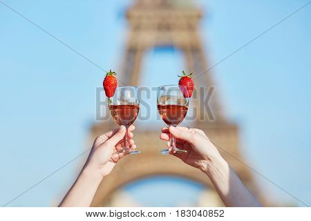Women Hands Holding Two Glasses Of Wine With The Eiffel Tower In The Background