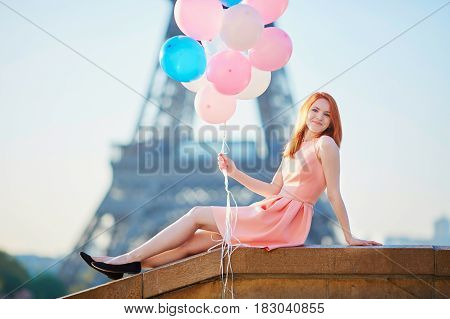 Young Woman In Pink Dress With Bunch Of Balloons In Paris Near The Eiffel Tower