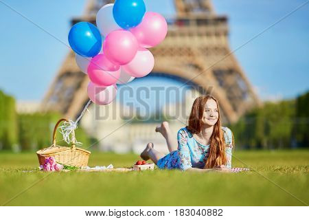 Young Woman Having Picnic Near The Eiffel Tower In Paris, France