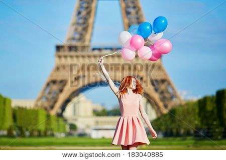 Woman In Pink Dress With Bunch Of Balloons Dancing Near The Eiffel Tower In Paris, France