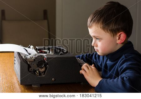Cute little boy typing a letter on a vintage black typewriter at home. Looking concentrated bored or in a bad mood