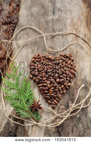 Unshelled Pine Nuts In Form Of Heart On Aged Wood