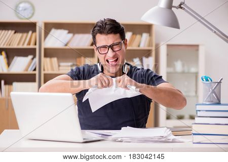 Angry man tearing apart his paperwork due to stress