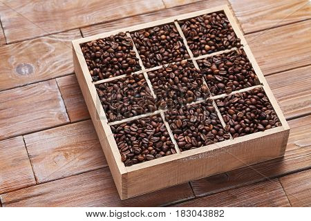 Roasted Coffee Beans In Wooden Basket On Brown Table