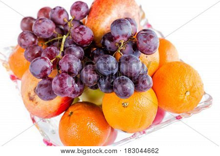 Oranges and grape in a bowl close uo isolated on white.