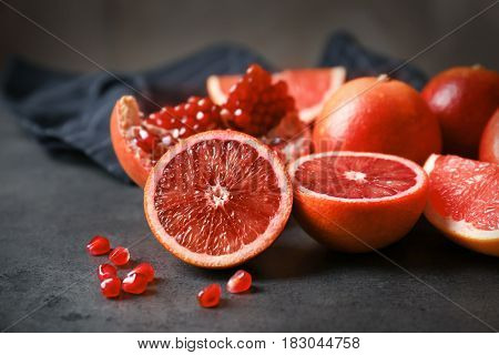 Heap of red citrus fruits and pomegranate on grunge background