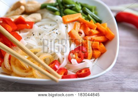 Plate with tasty rice noodle and vegetables on wooden table