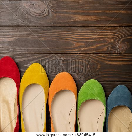 Row of colored shoes (ballerinas) on a dark wooden background. Selective focus.