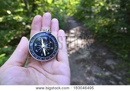 Woman hand holding compass on blurred forest background.Travel concept.Selective focus.