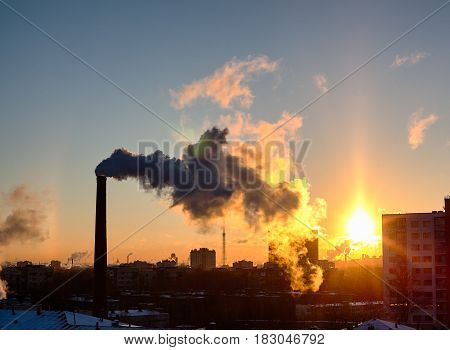 Smoke from industrial chimneys at sunset over the metropolis. A solar halo, a rainbow and snow. St. Petersburg