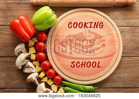 Cooking school concept. Cutting board and ingredients on wooden background