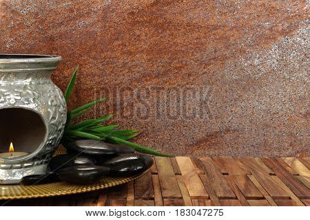 Heap of spa hot stones for massage with aroma lamp and bamboo on wooden background