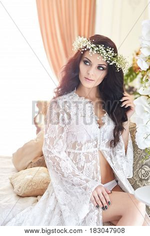 Beautiful bride in lingerie and with a wreath of flowers on her head in the morning before the wedding. White negligee of the bride preparing for the wedding ceremony. Sexy girl on the bed
