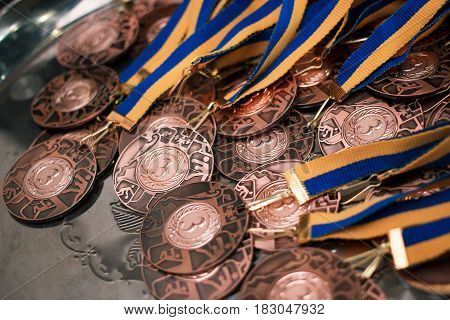 Many Bronze Medals With Yellow Blue Ribbons On A Silver Tray