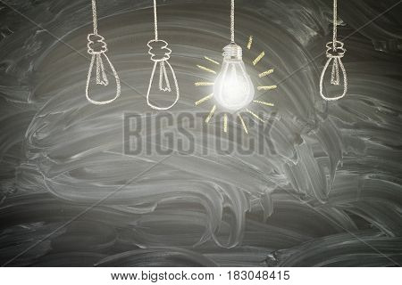 idea concept - row of light bulbs with bright glowing one on blackboard with copy space