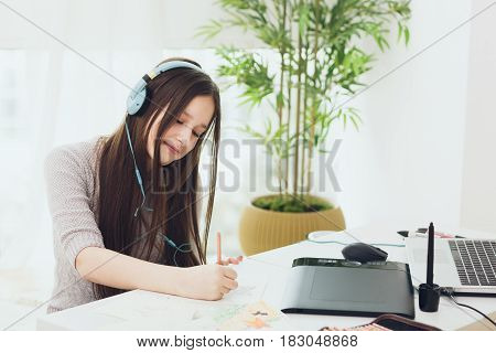 Teenage girl graphic designer using notebook and graphic tablet with stylus while studying at home