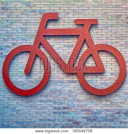 Bike route urban sign on brick wall, square toned image