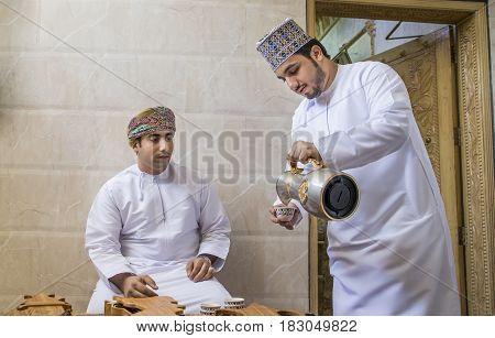 Nizwa Oman 26th May 2016: omani man serving traditional coffee called qahwa to another omani man