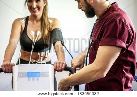 doctor visiting and monitoring a young girl during exercise with electrocardiogram