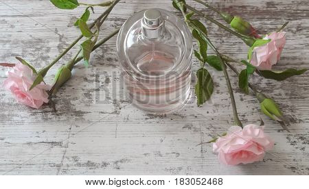 Perfume bottle with a delicate pink fragrance and roses on old wooden background